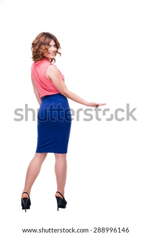 Back view portrait of a beautiful woman holding copyspace on palm isolated on a white background. Looking at camera - stock photo