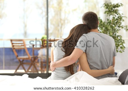 Back view portrait of a happy couple sitting on the bed looking the balcony outdoors through a window of the bedroom of a house - stock photo