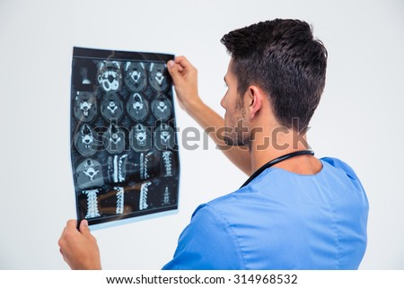 Back view portrait of a male doctor looking at x-ray picture of brain isolated on a white background