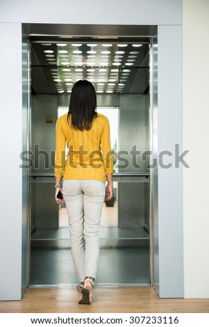 Back view portrait of a woman going in elevator indoors - stock photo