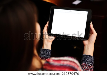 Back view portrait of a woman holding tablet computer - stock photo