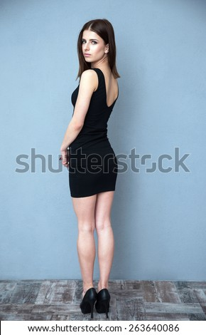 Back view portrait of a young beautiful woman looking at camera - stock photo