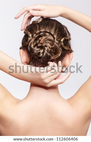 back view portrait of beautiful young dark blonde woman with creative plait hairdo on gray