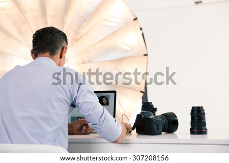 Back view portrait of photographer using laptop at his workplace - stock photo