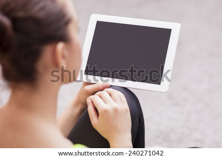 Back View Portrait of Woman Holding Tablet Computer. Focus on Tablet Computer. Horizontal Image - stock photo