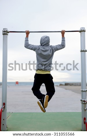 Back view portrait of  young bodybuilder in active wear doing pull ups on the horizontal bar outdoors, strong athlete doing exercise in a cloudy morning outside, fit man working out at street gym - stock photo