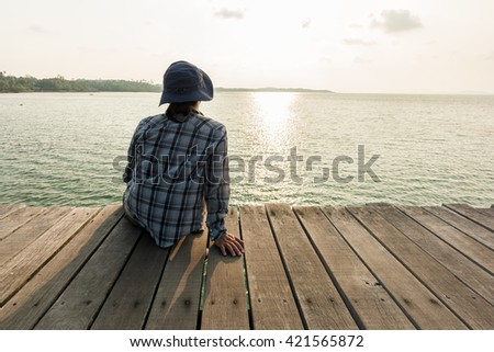 Back view portrait of young man sitting � against the sea on wooden floor pier at sunrise time. - stock photo
