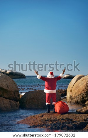 Back view shot of Santa Claus enjoying the seas air with his hands raised looking over the ocean with copyspace - stock photo
