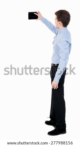 back view standing business man with tablet computer in hands of. Rear view people collection. backside view person. Isolated over white background. guy in office clothes photographed on a Tablet PC. - stock photo