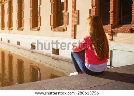 Back view trendy hipster enjoying sunny afternoon outdoors, teenager relaxing, young female looking thoughtful as sitting on the steps alone, young woman suffering from loneliness and depression - stock photo