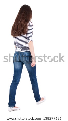 back view walking woman in jeans beautiful brunette girl in motion. backside view person. Rear view people collection. Isolated over white. girl in striped T-shirt with sleeves podkatannymi goes ahead - stock photo