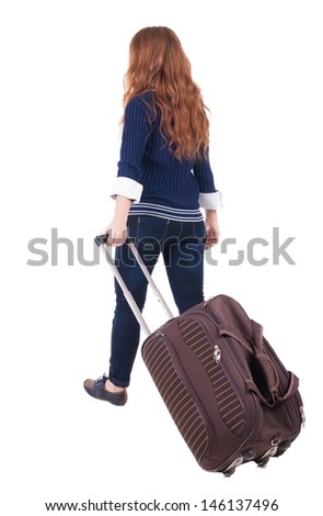 back view walking woman with suitcase. beautiful redhead girl in motion. backside view person. Rear view people collection. Isolated over white background. red-haired girl rolls  travel bag on wheels
