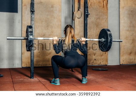 Back view young adult girl doing heavy duty squat in gym with barbell. Woman with perfect abs doing squat exercises. Blonde fit woman in great shape. Fitness - stock photo