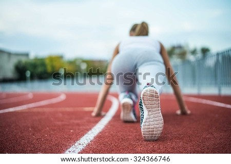 Back view. Young girl legs in stylish sneakers back side on a red race track of a stadium with white lane lines on background. Unrecognizable photo with copy space for inscription or objects