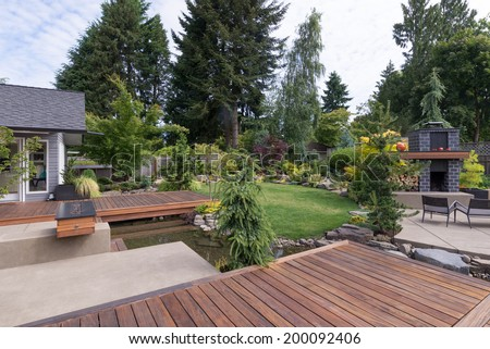 Back yard of a contemporary Pacific Northwest home featuring a deck a spanning creek-like water feature with a landscaped lawn and custom patio fireplace in the background. - stock photo