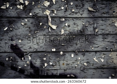 Backdrop of an old and weathered noticeboard. This empty surface is perfect as copy space or textured background. Bits of paper is stuck to the staples that are attached to the billboard. - stock photo