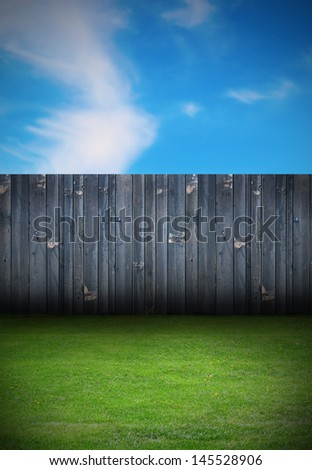 backdrop of backyard with old black wooden fence and green grass - stock photo