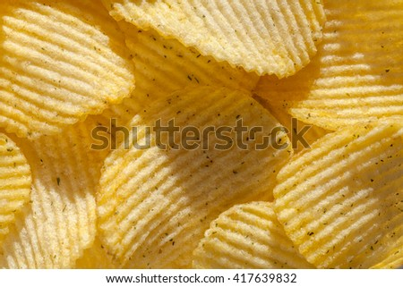 Backdrop of delicious potato chips with spices. Closeup