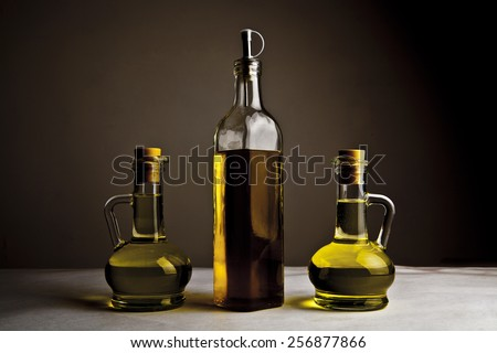 Backdrop of three olive oil glass transparent bottle with cork stand on white table on kitchen space room, on dark black  background Empty space for inscription  - stock photo