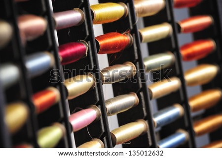 Background assortment of silk thread spools of different shades of color