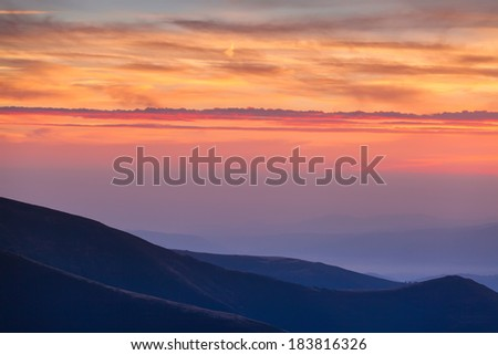 Background, beautiful, warm, bright colors of sunrise. In the mountains, stands a light mist over the countryside and the fresh air of freedom. Cloudy sky illuminated by the sun.