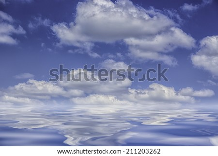 Background blue sky fluffy clouds reflected on ocean water - stock photo