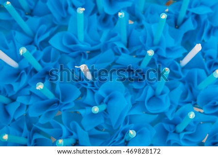 Background blur of blue candles and paper.