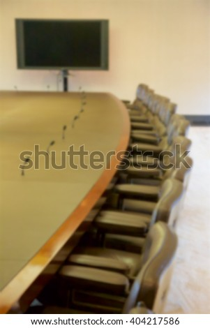 Background blur of empty seats at a board room table.