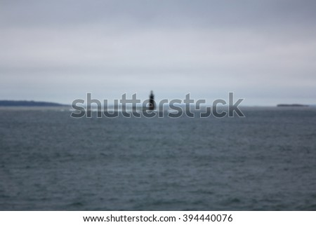 Background blur of tiny lighthouse amid a vast gray sea. - stock photo