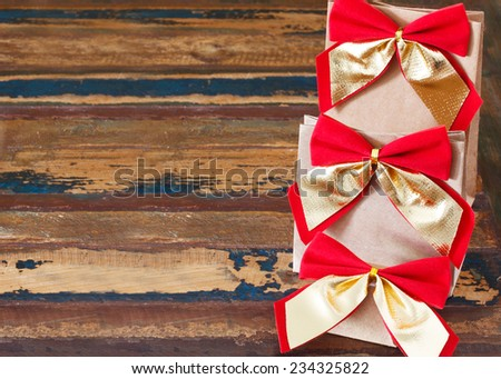 Background: christmas gifts paper package with red golden bow. Selective focus on bow. Copy space - stock photo