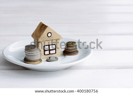 Background concepts house with the coins on a plate/payment for a house with a plot