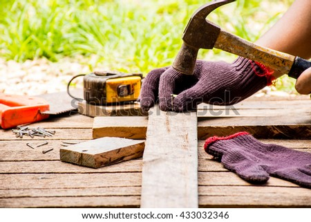 Background Craftsman tool such as old hammer with tape measure and small nails and saw with glove and working outdoor view.Background for carpenter and repair and craft country style. - stock photo