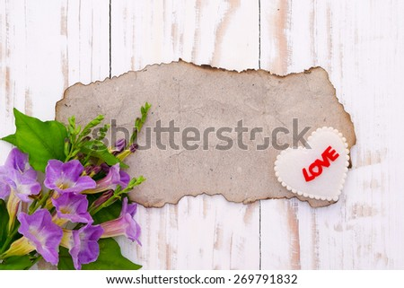 Background for greetings,Blank old brown paper with flowers and heart shape on wood table