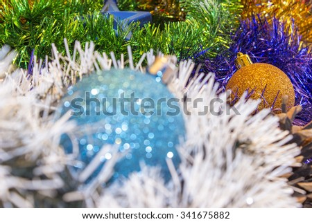 Background for New Year's and Christmas cards. Celebratory  holiday bright rainbow decorations for Christmas trees or pine. Focus on  yellow toy - stock photo