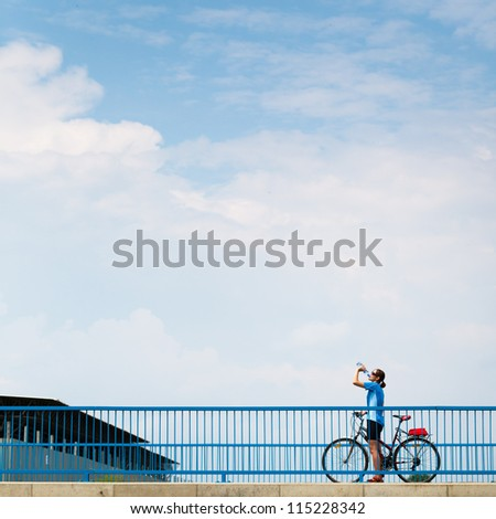 Background for poster or advertisment pertaining to cycling/sport/outdoor activities - female cyclist during a halt on a bridge against blue sky (color toned image) - stock photo