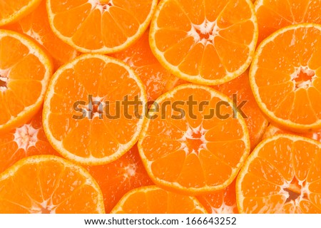 Background from overlapping slices of juicy seedless satsumas (Citrus unshiu) - stock photo