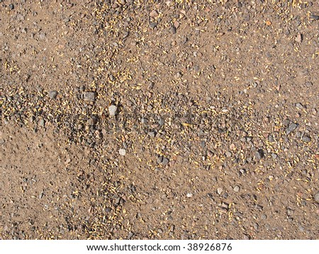 Background from pieces of the brown earth and the rumpled yellow grass and pebbles - stock photo