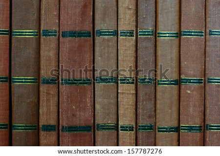 Background from shabby covers of old books, these books are placed vertically in the same row - stock photo