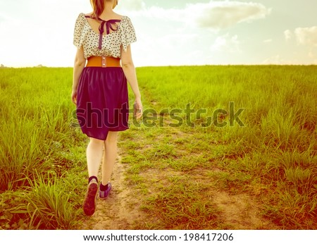 Background girl in a dress and sneakers walking on a footpath in a field of view from behind - stock photo
