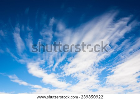 Background image of deep blue sky with dramatic streaky clouds - stock photo