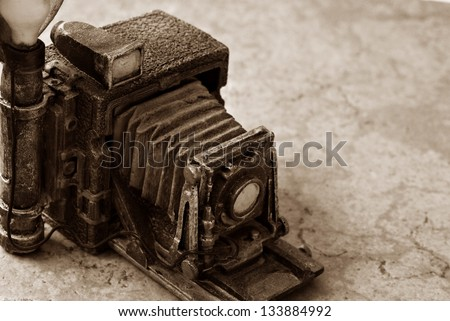 Background image of miniature vintage accordion style camera (model made from resin) on marbled tile.  Macro image in sepia tones with shallow dof and copy space. - stock photo
