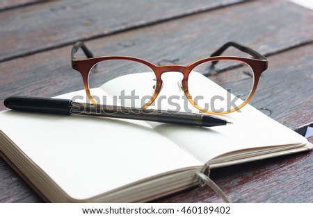 Background image of pen, glasses and pocket notebook on the table