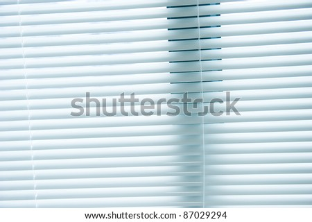 background image of white mini blinds inside home closed. - stock photo