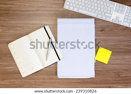 Background image wit assorted items, used for planning: a calendar, and notepad, pen, yellow sticky notes and a keyboard, on a wooden surface - stock photo