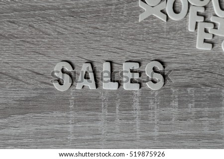 "Background. Letters on wooden table. ""Sales""."