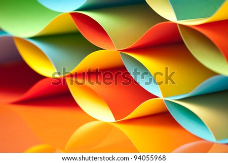 background macro image of colorful origami pattern made of curved sheets of paper, with mirror reflexion - stock photo