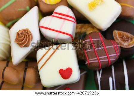 Background made of assorted milk, white and dark chocolates and pralines  - stock photo