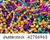 Background made up of mulit-colored including gold, purple, blue, green and pink mardi gras beads - stock photo