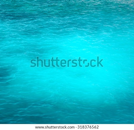 Background of a bright turquoise ocean water with gentle ripples - stock photo