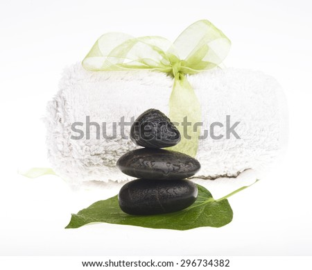 Background of a spa with black stones on a green leaf and white towel with a ribbon. - stock photo